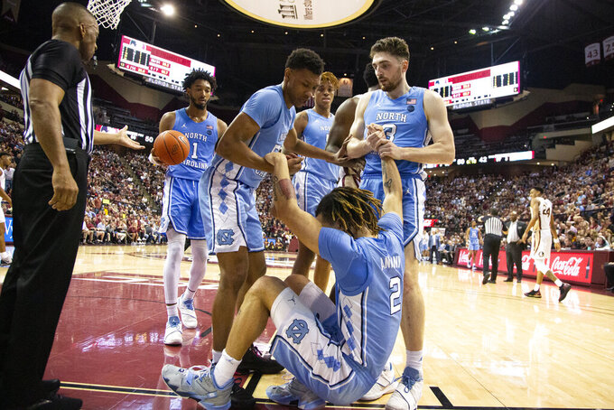 North Carolina guard Cole Anthony (2) is picked up by his teammates after Florida State was penalized for charging in the second half of an NCAA college basketball game in Tallahassee, Fla., Monday, Feb. 3, 2020. Florida State defeated North Carolina 65-59. (AP Photo/Mark Wallheiser)