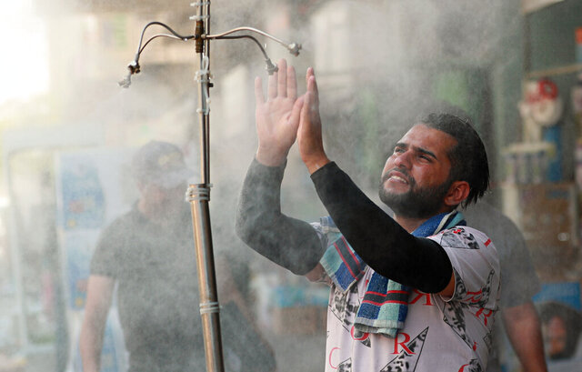 A man cools off from the summer heat under an open air shower in Baghdad, Iraq, Sunday, July 5, 2020. (AP Photo/Hadi Mizban)