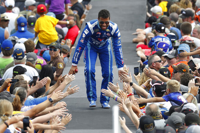 Bubba Wallace greets fans before a NASCAR Cup Series auto race at Michigan International Speedway in Brooklyn, Mich., Sunday, Aug. 11, 2019. (AP Photo/Paul Sancya)