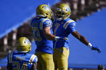 From right to left, UCLA defensive back Mo Osling III, celebrates with Bo Calvert  in front of UCLA defensive back Qwuantrezz Knight after breaking up a pass in the end zone for California wide receiver Makai Polk during the second half of an NCAA college football game in Los Angeles, Sunday, Nov. 15, 2020. (AP Photo/Kelvin Kuo)