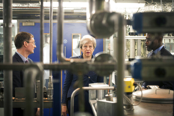 Britain's Prime Minister Theresa May during a visit to Imperial College where she saw machinery which converts carbon dioxide into oxygen, in London, Wednesday, June 12, 2019. Britain's outgoing prime minister on Wednesday announced plans to eliminate the country's net contribution to climate change by 2050 as Europe's effort to slow global warming picked up speed. (Stefan Rousseau/Pool photo via AP)