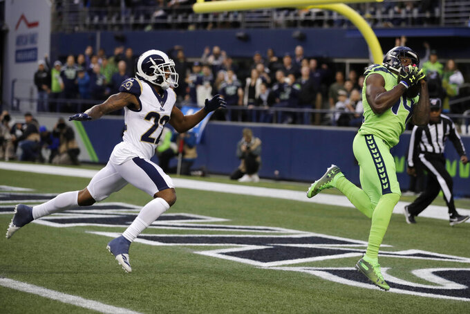 Seattle Seahawks wide receiver DK Metcalf, right, catches a pass for a touchdown ahead of Los Angeles Rams cornerback Marcus Peters (22) during the first half of an NFL football game Thursday, Oct. 3, 2019, in Seattle. (AP Photo/Stephen Brashear)