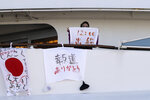 FILE - In this Feb. 11, 2020, file photo, a woman holds a piece of cloth with the ship's departure time written on it while quarantined on the Diamond Princess cruise ship at the Yokohama Port in Yokohama, near Tokyo. Life on board the luxury cruise ship, which has dozens of cases of a new virus, can include fear, excitement and soul-crushing boredom, according to interviews by The Associated Press with passengers and a stream of tweets and YouTube videos. (AP Photo/Jae C. Hong, File)