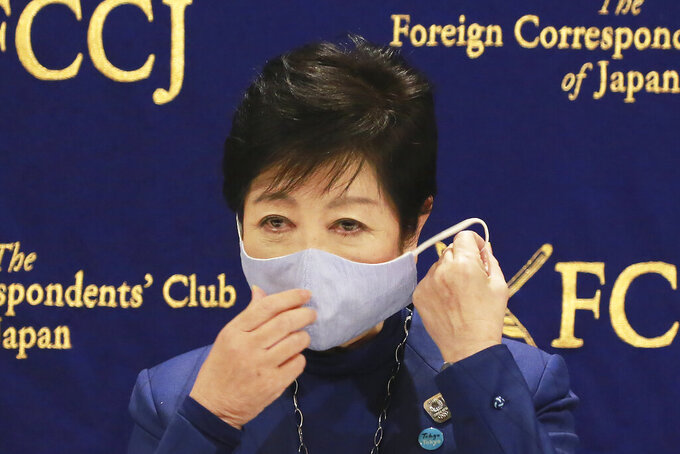 Tokyo Gov. Yuriko Koike takes off her mask as she speaks at a news conference in Tokyo, Tuesday, Nov. 24, 2020. Koike remains firm about being able to safely hold the Olympics next year despite growing concerns about Japan's recent resurgence of COVID-19 infections. (AP Photo/Koji Sasahara)