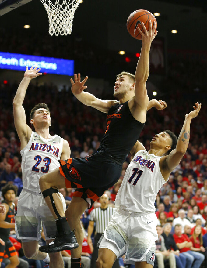 Oregon State forward Tres Tinkle (3) drives between Arizona guard Alex Barcello and Ira Lee (11) in the first half during an NCAA college basketball game, Saturday, Jan. 19, 2019, in Tucson, Ariz. (AP Photo/Rick Scuteri)