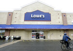 FILE - In this Feb. 23, 2018, file photo a cyclist rides near an entrance to a Lowe's retail home improvement and appliance store, in Framingham, Mass. Lowe's Cos. delivered weaker-than-expected sales for the fiscal fourth quarter and offered an annual forecast that came below Wall Street expectations. The report, issued Wednesday, Feb. 26, 2020, sent shares down in early morning trading. (AP Photo/Steven Senne, File)