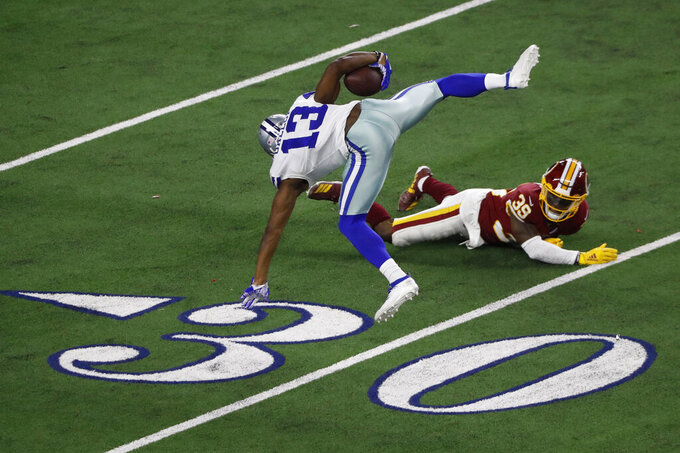 Dallas Cowboys wide receiver Michael Gallup (13) is upended and thrown off balance by Washington Redskins defensive back Jeremy Reaves (39) as he runs for a touchdown after a catch during the second half of an NFL football game in Arlington, Texas, Sunday, Dec. 15, 2019. (AP Photo/Roger Steinman)