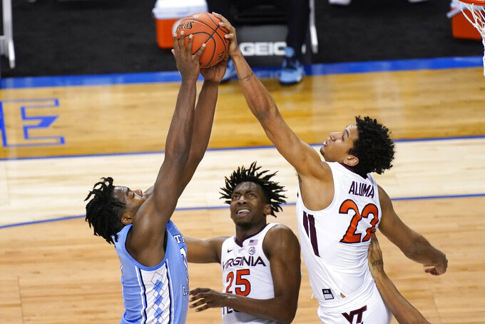 Virginia Tech guard Tyrece Radford (23) blocks the shot of North Carolina forward Day'Ron Sharpe (11) as Virginia Tech forward Justyn Mutts (25) looks on during the second half of an NCAA college basketball game in the quarterfinal round of the Atlantic Coast Conference tournament in Greensboro, N.C., Thursday, March 11, 2021. (AP Photo/Gerry Broome)