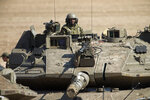An Israeli soldier drives a tank at a gathering area near the Israel-Gaza border, in southern Israel, Tuesday, March 26, 2019. Israeli Prime Minister Benjamin Netanyahu returned home from Washington on Tuesday, heading straight into military consultations after a night of heavy fire as Israeli aircraft bombed Gaza targets and the strip's militants fired rockets into Israel. (AP Photo/Ariel Schalit)
