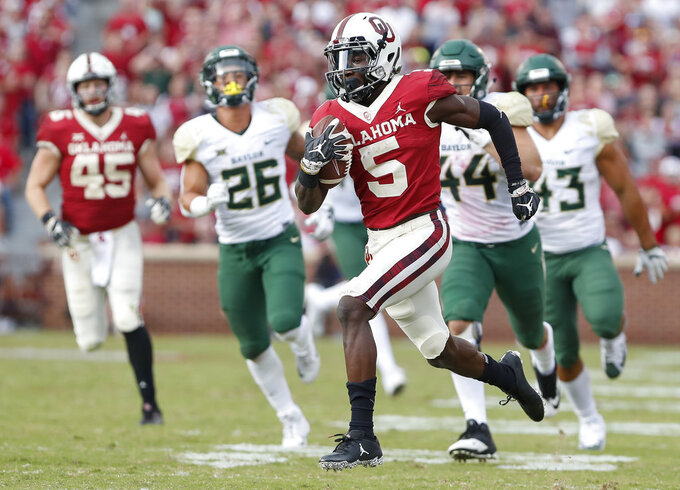 FILE - In this Sept. 29, 2018, file photo, Oklahoma wide receiver Marquise Brown (5) runs ahead of Baylor in the second half of an NCAA college football game in Norman, Okla. Oklahoma quarterback Kyler Murray has star receivers in Brown and CeeDee Lamb, yet he doesn't hesitate to throw to other options. (AP Photo/Alonzo Adams, File)