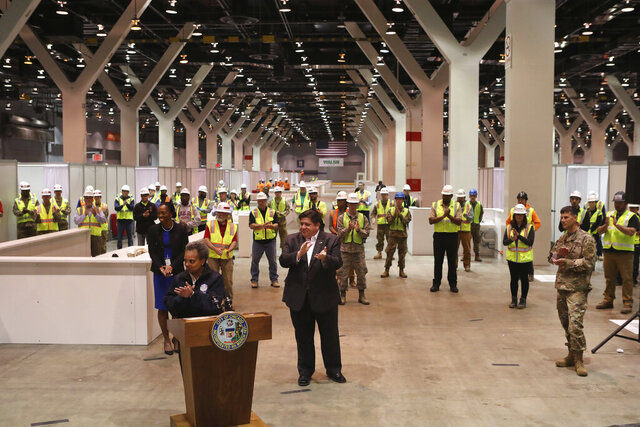 "Illinois Gov. J.B. Pritzker, center, and Chicago Mayor Lori Lightfoot, at podium, applaud during a conference in Hall C Unit 1 of the COVID-19 alternate site at McCormick Place in Chicago on Friday, April 3, 2020. The ""alternative care facility"" is designed to relieve pressure on city hospitals from rapidly mounting coronavirus cases. (Chris Sweda/Chicago Tribune via AP, Pool)"