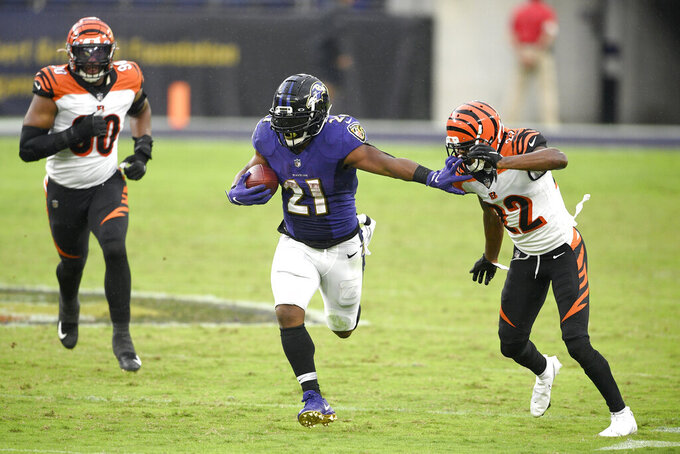 Baltimore Ravens running back Mark Ingram (21) runs with the ball as Cincinnati Bengals cornerback William Jackson (22) tries to stop him during the second half of an NFL football game, Sunday, Oct. 11, 2020, in Baltimore. (AP Photo/Nick Wass)