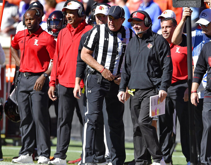 Louisville head coach Bobby Petrino talks with an official during the first half of an NCAA college football game against Clemson, Saturday, Nov. 3, 2018, in Clemson, S.C. (AP Photo/Richard Shiro)