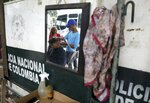 Carlos Herrera cuts the hair of a migrant, right next to the Simon Bolivar International Bridge which connects Colombia with Venezuela in La Parada, near Cucuta, Colombia, on the border with Venezuela, Tuesday, Feb. 19, 2019. Herrera earns one dollar with 30 cents for each haircut. AP Photo/Fernando Vergara)