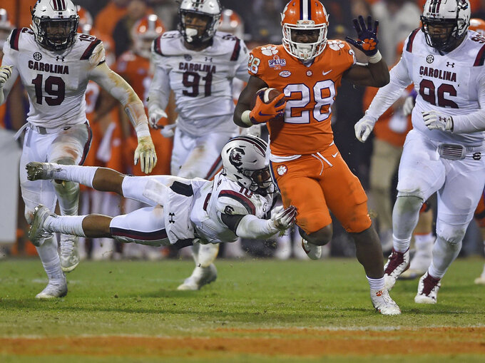 Clemson's Tavien Feaster (28) outruns the tackle attempt by South Carolina's R.J. Roderick during the second half of an NCAA college football game Saturday, Nov. 24, 2018, in Clemson, S.C. (AP Photo/Richard Shiro)