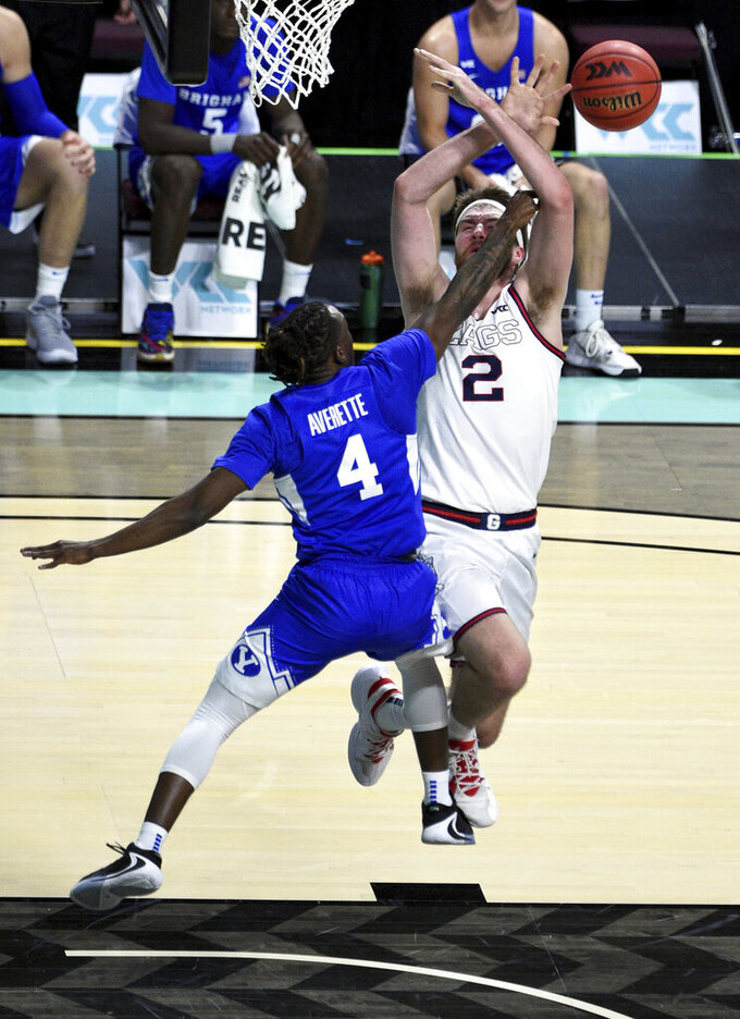 BYU guard Brandon Averette (4) defends against Gonzaga forward Drew Timme during the first half of an NCAA college basketball game for the West Coast Conference men's tournament championship Tuesday, March 9, 2021, in Las Vegas. (AP Photo/David Becker)