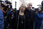 Sex abuse survivors, Denise Buchanan, left, and Peter Isely, both founding members of the ECA (Ending Clergy Abuse) make their way through a crowd of journalists on the occasion of their meeting with organizers of the summit on preventing sexual abuse at the Vatican, Wednesday, Feb. 20, 2019. A dozen survivors of clergy sexual abuse met with organizers of Pope Francis' landmark summit on preventing abuse and protecting children. Chilean survivor Juan Carlos Cruz, who was asked by the Vatican to invite survivors to the meeting, told reporters Wednesday that Francis would not be attending, as had been rumored. (AP Photo/Gregorio Borgia)