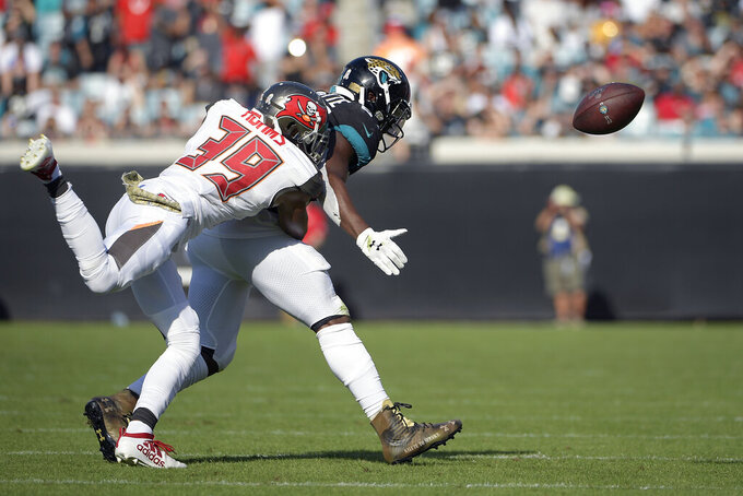 Tampa Bay Buccaneers strong safety Andrew Adams (39) breaks up a pass intended for Jacksonville Jaguars running back Leonard Fournette, right, during the second half of an NFL football game, Sunday, Dec. 1, 2019, in Jacksonville, Fla. (AP Photo/Phelan M. Ebenhack)