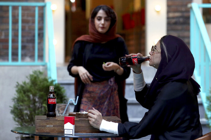 An Iranian drinks a Coca-Cola and smokes a Marlboro cigarette at a cafe in downtown Tehran, Iran, Wednesday, July 10, 2019. Whether at upscale restaurants or corner stores, American brands like Coca-Cola and Pepsi can be seen throughout Iran despite the heightened tensions between the two countries. U.S. sanctions have taken a heavy toll, but Western food, movies, music and clothing are still widely available. (AP Photo/Ebrahim Noroozi)