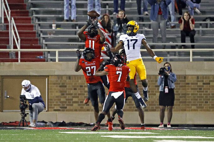 Texas Tech's Eric Monroe (11) breaks up the final play of the game during the second half of an NCAA college football game against West Virginia, Saturday, Oct. 24, 2020, in Lubbock, Texas. (AP Photo/Brad Tollefson)
