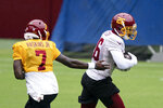 Washington quarterback Dwayne Haskins Jr. (7) hands the ball off to running back Adrian Peterson (26) during an NFL football practice at FedEx Field, Monday, Aug. 31, 2020, in Washington. (AP Photo/Alex Brandon)