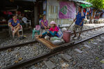 A vendor pushes an improvised cart with a woman and merchandise along a rarely used rail track in Bangkok, Thailand, Thursday, June 25, 2020. Daily life in the capital slowly returns to normal as the Thai government eases many restrictions imposed weeks ago to combat the spread of COVID-19. Though emergency regulations require the use of face masks in public, some residents have become apathetic as Thailand has record zero local transmission for over three weeks. (AP Photo/ Gemunu Amarasinghe)