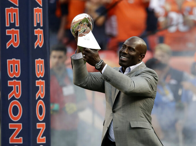 FILE - In this Sept. 8, 2016, file photo, Super Bowl XXXII MVP Terrell Davis carries the Lombardi Trophy onto the field prior to an NFL football game between the Denver Broncos and the Carolina Panthers, in Denver. The coronavirus pandemic scuttled most college pro days, wiped out all rookie minicamps and obliterated the NFL's traditional offseason, making it became almost impossible for long shots to make their mark and, consequently, the 53-man roster. Among them: Hall of Famer Terrell Davis. Davis ended the frustrations of a long-suffering franchise, city and larger-than-life quarterback who could never win the big game before he came along. (AP Photo/Jack Dempsey, File)