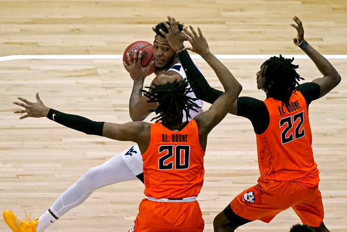 West Virginia's Derek Culver, rear, looks top pass under pressure from Oklahoma State's Keylan Boone (20) and Kalib Boone (22) during the first half of an NCAA college basketball game in the second round of the Big 12 Conference tournament in Kansas City, Mo., Thursday, March 11, 2021. (AP Photo/Charlie Riedel)
