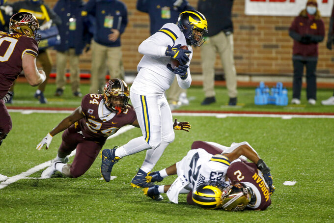 Michigan defensive lineman Donovan Jeter (95) catches the ball en route to a touchdown past running back Mohamed Ibrahim (24) after linebacker Michael Barrett (23) knocked it loose from Minnesota quarterback Tanner Morgan (2) in the first quarter of an NCAA college football game Saturday, Oct. 24, 2020, in Minneapolis. (AP Photo/Bruce Kluckhohn)