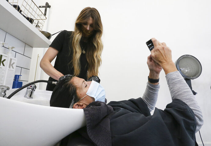 Leslie Musumecci checks a text while Emily Summerville rinses her hair Monday, May 11, 2020 at The Nook on 7th Street in Tuscaloosa, Ala. the first time since mid-March when personal contact businesses were shut down due to COVID-19 restrictions. Summerville owns The Nook with her husband. She said they had fielded many calls for appointments and were doing their best to accommodate those who had waited the longest to get them in first.  (Gary Cosby Jr./Tuscaloosa News via AP)