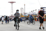 A woman rides her bicycle on the boardwalk at Coney Island during the current coronavirus outbreak, Sunday, May 24, 2020, in New York, during the Memorial Day weekend, which marks the traditional beginning of summer. (AP Photo/Kathy Willens)