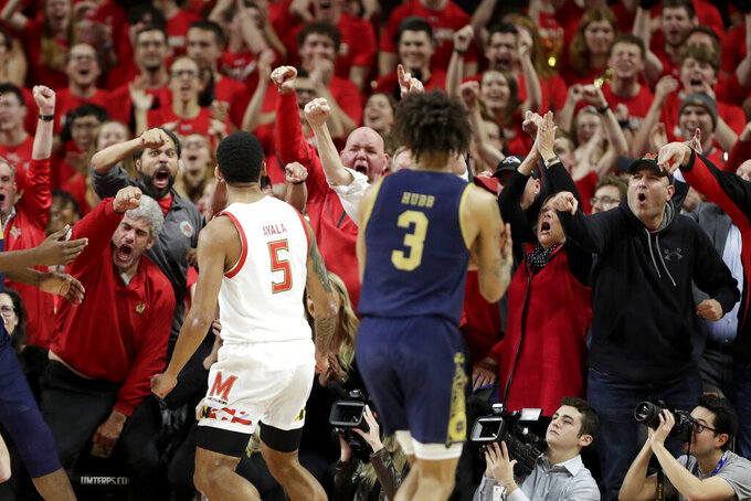 Fans react after Maryland guard Eric Ayala (5) dunked as Notre Dame guard Prentiss Hubb (3) looks on during the first half of an NCAA college basketball game, Wednesday, Dec. 4, 2019, in College Park, Md. (AP Photo/Julio Cortez)