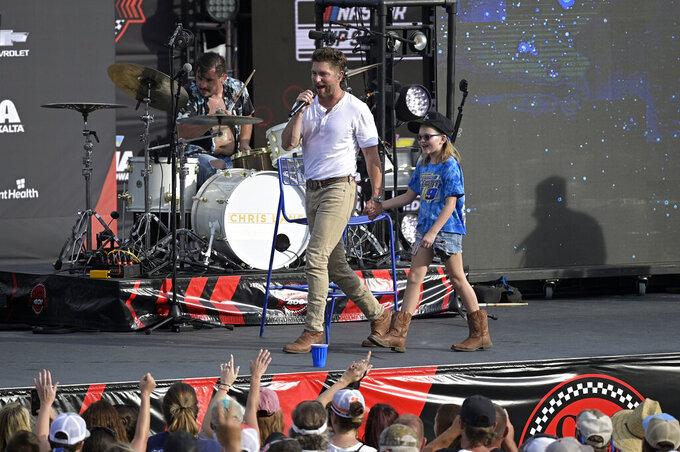 Entertainer Chris Lane, left, performs with a fan before a NASCAR Cup Series auto race at Daytona International Speedway, Saturday, Aug. 28, 2021, in Daytona Beach, Fla. (AP Photo/Phelan M. Ebenhack)
