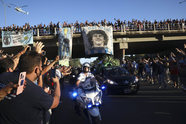 Mourning fans wave from an overpass at the caravan carrying the remains of Diego Maradona to his resting place in Buenos Aires, Argentina, Thursday, Nov. 26, 2020. The Argentine soccer great who was among the best players ever and who led his country to the 1986 World Cup title died from a heart attack at his home Wednesday, at the age of 60. (AP Photo/Rodrigo Abd)
