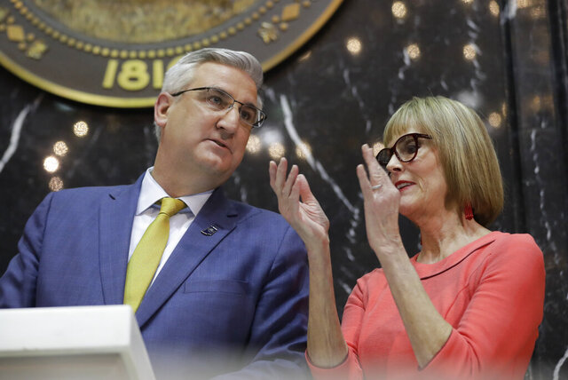 Indiana Gov. Eric Holcomb speaks with Lt. Gov. Suzanne Crouch as he delivers his State of the State address to a joint session of the legislature at the Statehouse, Tuesday, Jan. 14, 2020, in Indianapolis. (AP Photo/Darron Cummings)
