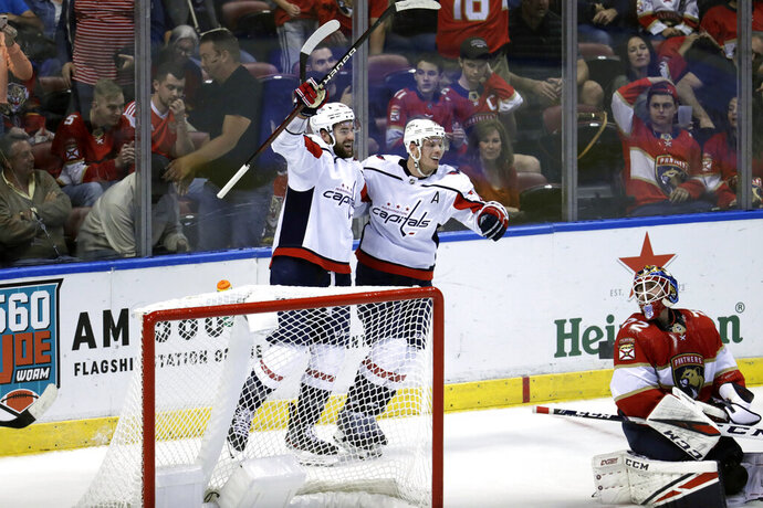 Washington Capitals right wing Tom Wilson, left, celebrates with defenseman John Carlson after scoring a goal against Florida Panthers goaltender Sergei Bobrovsky (72) during overtime of an an NHL hockey game, Thursday, Nov. 7, 2019, in Sunrise, Fla. (AP Photo/Lynne Sladky)