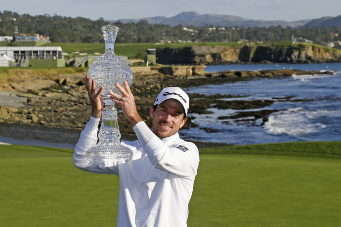 FILE - In this Feb. 9, 2020, file photo, Nick Taylor, of Canada, holds up his trophy on the 18th green of the Pebble Beach Golf Links after winning the AT&T Pebble Beach National Pro-Am golf tournament in Pebble Beach, Calif. The win got him into his first Masters, but Taylor will miss out on the roars without spectators. (AP Photo/Eric Risberg, File)