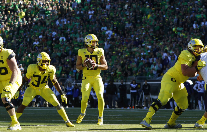 Oregon quarterback Justin Herbert (10), sets up for a touchdown pass at the end of the second quarter to tie the game against Washington during an NCAA college football game in Eugene, Ore., Saturday, Oct. 13, 2018. (AP Photo/Thomas Boyd)