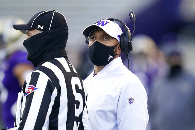Washington coach Jimmy Lake stands with official Michael Weseloh as he waits for a review of a call during the second half of the team's NCAA college football game against Stanford on Saturday, Dec. 5, 2020, in Seattle. (AP Photo/Elaine Thompson)