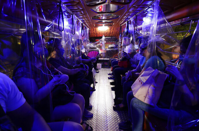 Plastic sheets on a traditional Jeepney bus separate passengers as part of health measures to help prevent the spread of the new coronavirus in metropolitan Manila, Philippines on Friday, July 3, 2020. The government is allowing some routes for Jeepneys to be opened to help public transportation as the government slowly eases the coronavirus lockdown (AP Photo/Aaron Favila)