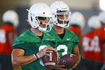 FILE - In this Thursday, Aug. 1, 2019 file photo, Oklahoma State quarterbacks Dru Brown, left, and Spencer Sanders, right, listen to instructions during NCAA college football practice in Stillwater, Okla. (AP Photo/Sue Ogrocki, File)