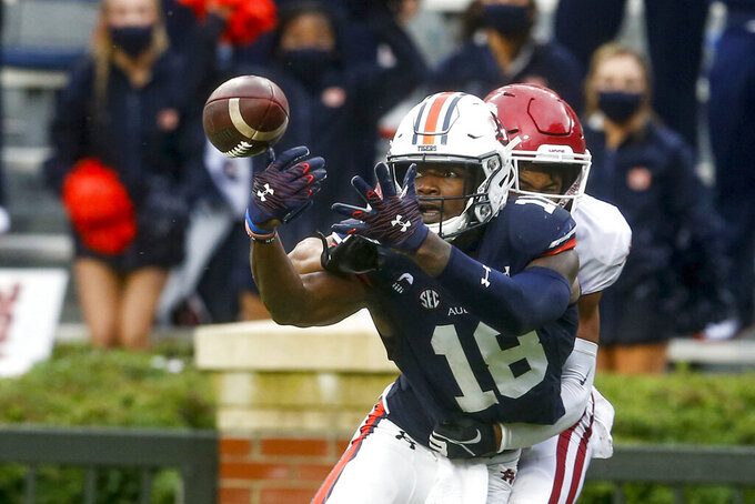 Auburn wide receiver Seth Williams (18) tries to catch a pass as Arkansas defensive back Khari Johnson (19) defends during the second quarter of an NCAA college football game on Saturday, Oct. 10, 2020, in Auburn, Ala. (AP Photo/Butch Dill)