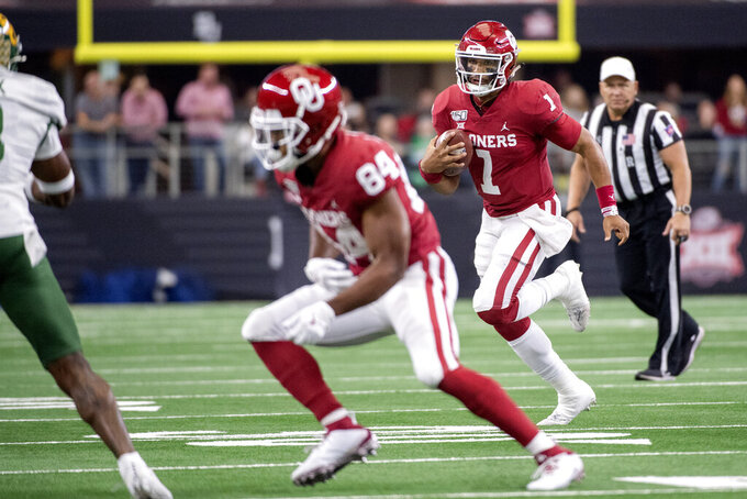 Oklahoma quarterback Jalen Hurts (1) runs behind the blocking of Oklahoma wide receiver Lee Morris (84) during the second half of an NCAA college football game for the Big 12 Conference championship, Saturday, Dec. 7, 2019, in Arlington, Texas. Oklahoma won 30-23 in overtime. (AP Photo/Jeffrey McWhorter)