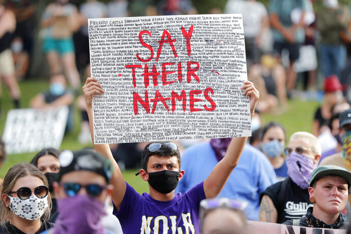 A man holds up a signy during a peaceful rally in downtown New Orleans, Tuesday, June 2, 2020. They were protesting over the death of George Floyd, a black man who was in police custody in Minneapolis. Floyd died after being restrained by Minneapolis police officers on Memorial Day. (AP Photo/Gerald Herbert)