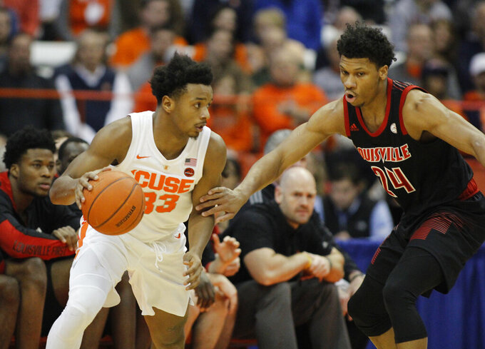 Syracuse's Elijah Hughes, left, dribbles around Louisville's Dwayne Sutton, right, during the first half of an NCAA college basketball game in Syracuse, N.Y., Wednesday, Feb. 20, 2019. (AP Photo/Nick Lisi)
