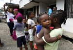 A group of children wait to be blessed by Catholic Bishop Ruben Dario Jaramillo Montoya, background, in Buenaventura, Colombia, Saturday, July 13, 2019. Jaramillo traveled on a fire truck to some of Buenaventura's most crime-ridden neighborhoods on Saturday, sprinkling water that he had blessed in what he called an attempt to thwart drug trafficking gangs and other illegal groups. (AP Photo/Fernando Vergara)