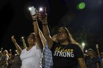 Karina Cardoso and Linda Nevarez hold their cellphone flashlights up during a vigil  Sunday, Aug. 4, 2019, at Ponder Park in honor to the victims of a mass shooting occurred in Walmart on Saturday, Aug. 3, 2019, in El Paso, Texas.  (Lola Gomez/Austin American-Statesman via AP)