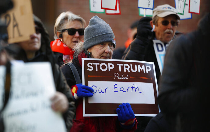 A protester holds a placard at a rally of advocates to voice opposition to efforts by the Trump administration to weaken the National Environmental Policy Act, which is the country's basic charter for protection of the outdoors on Tuesday, Feb. 11, 2020, in Denver. (AP Photo/David Zalubowski)