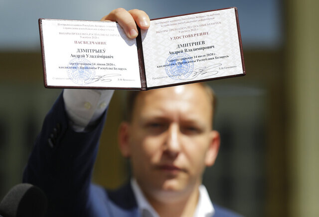 Andrei Dmitriyev shows his presidential candidate's identification card after he was registered as a candidate for the presidential elections in Minsk, Belarus, Tuesday, July 14, 2020. The election commission has cleared Belarusian President Alexander Lukashenko and four other candidates for running in a presidential vote in August, but denied registration to Lukashenko's two main aspiring challengers. (AP Photo/Sergei Grits)