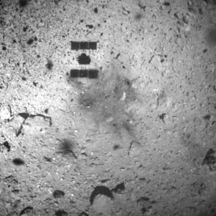 This image released by the Japan Aerospace Exploration Agency (JAXA) shows the shadow, center above, of the Hayabusa2 spacecraft after its successful touchdown on the asteroid Ryugu Friday, Feb. 22, 2019. Hayabusa2 touched down on the distant asteroid Friday on a mission to collect material that could provide clues to the origin of the solar system and life on Earth. (JAXA via AP)